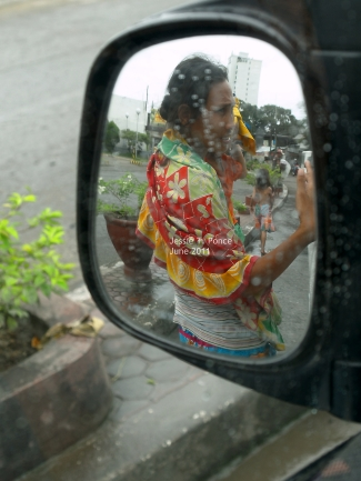 A lady begs for coins by my car window