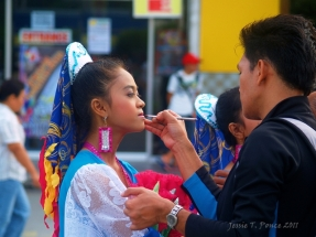 A street dancer gets finishing touches on her make up