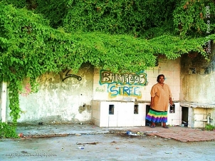 A Nauruan lady waits for the bus by a colorful ruin
