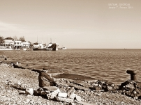 An old man sits alone by the docks