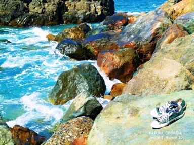 A pair of shoes by colorful beach rocks