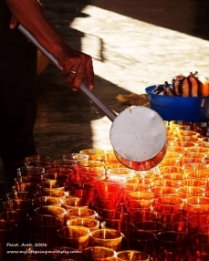 A row of glasses is being filled with drinks for a village feast